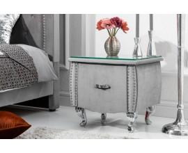 Jedinečný moderný nočný stolík Caledonia striebornej farby s kovovými cvokmi a so sklenenou doskou na strieborných nožičkách