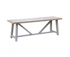 Dizajnová jedálenská lavica Nyakim z hnedého dreveného masívu a drevenými nožičkami s podstavou v tvare V